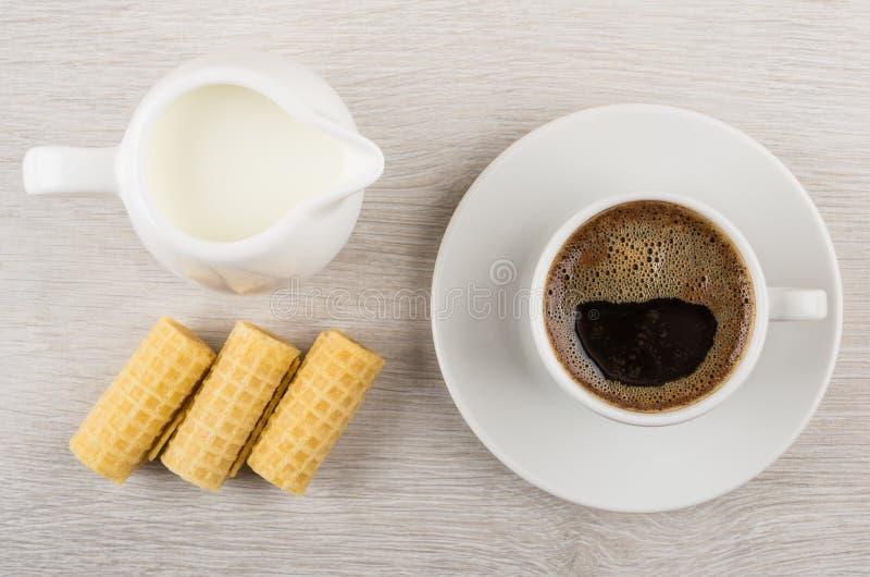 La taza de café, leche en el jarro, oblea rueda en la tabla de madera foto de archivo libre de regalías