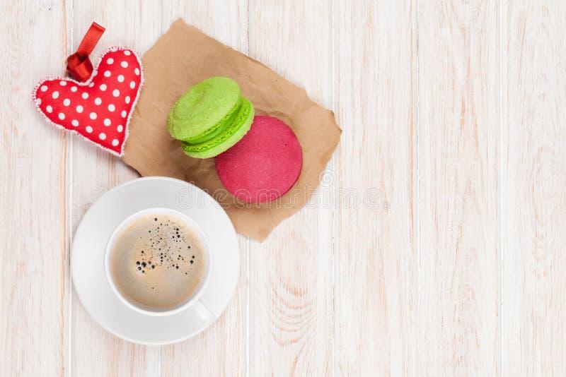 La taza de café, los macarons coloridos y el regalo del día de tarjetas del día de San Valentín juegan fotos de archivo