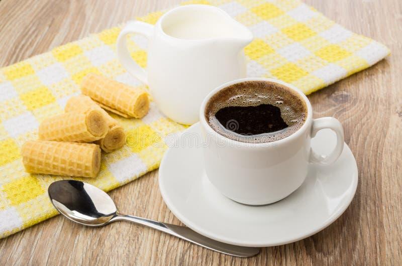 La taza de café, oblea rueda en servilleta y la cuchara amarillas fotografía de archivo