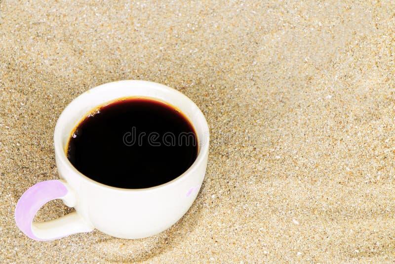 La taza de café puso en arena en la playa foto de archivo