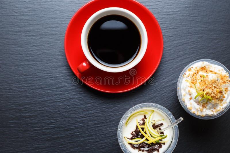 La taza de café roja con se lleva los postres imágenes de archivo libres de regalías