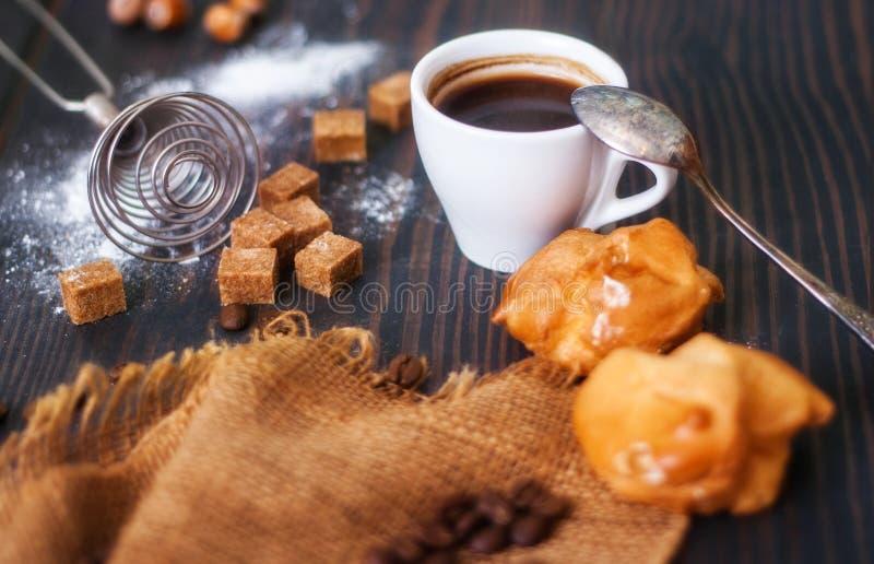 La taza de café sólo caliente con el hogar hizo profiteroles en una tabla rústica imagenes de archivo