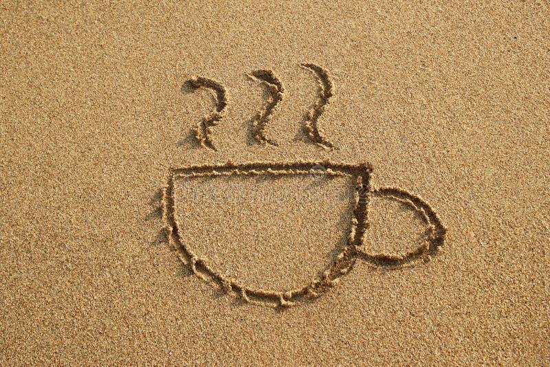 La taza de café se dibuja en una playa de la arena en una puesta del sol fotos de archivo libres de regalías