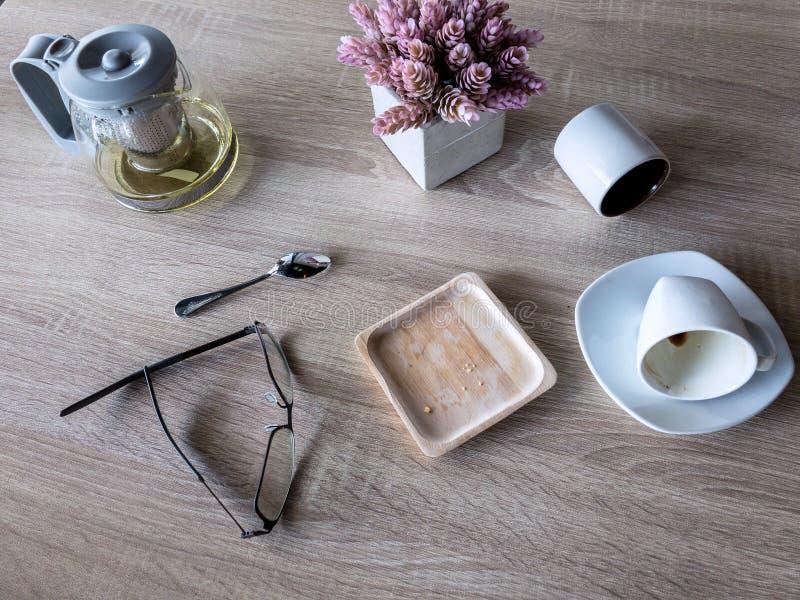 La taza de café usada y la taza de té incluyendo los vidrios colocan en la tabla de madera imágenes de archivo libres de regalías