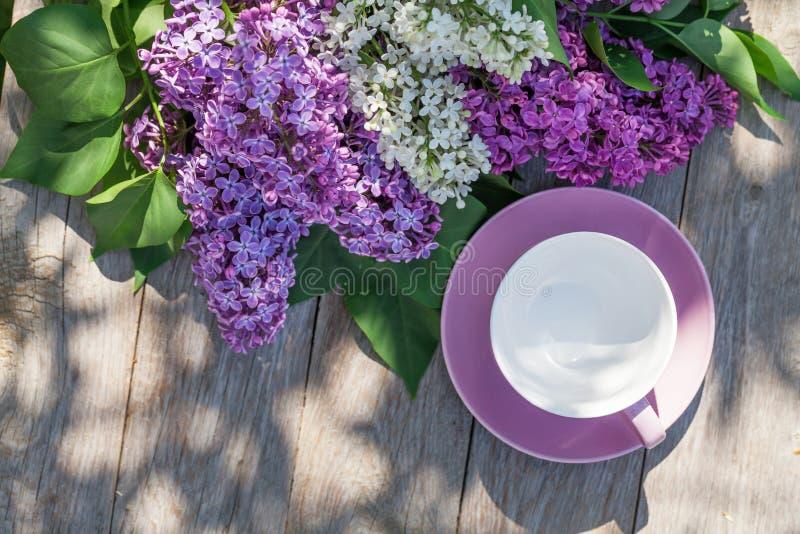 La taza de café y la lila colorida florece en la tabla del jardín fotos de archivo