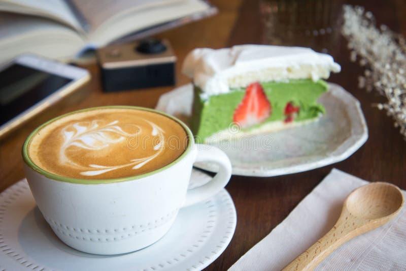 La taza de café y la torta sabrosa relajan el libro del tiempo y el teléfono móvil en TA foto de archivo