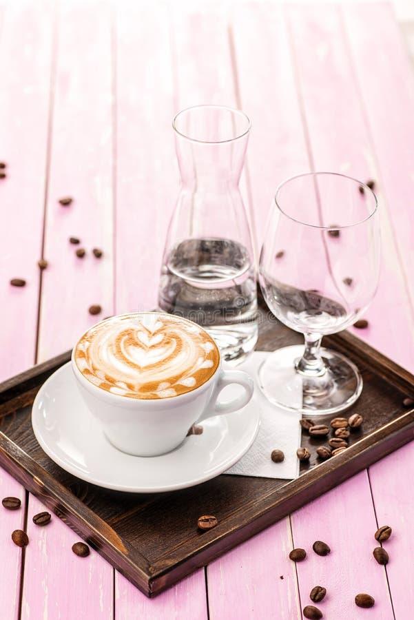 La taza de capuchino con la espuma del corazón, sistema de la taza de café con los granos de café en fondo de madera rosado, bebe foto de archivo libre de regalías