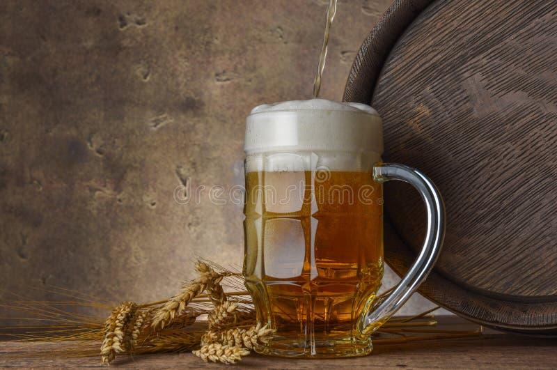 La taza de cerveza con los oídos del trigo y el barril de madera en un fondo oscuro de la pared, vierten la cerveza imagen de archivo libre de regalías