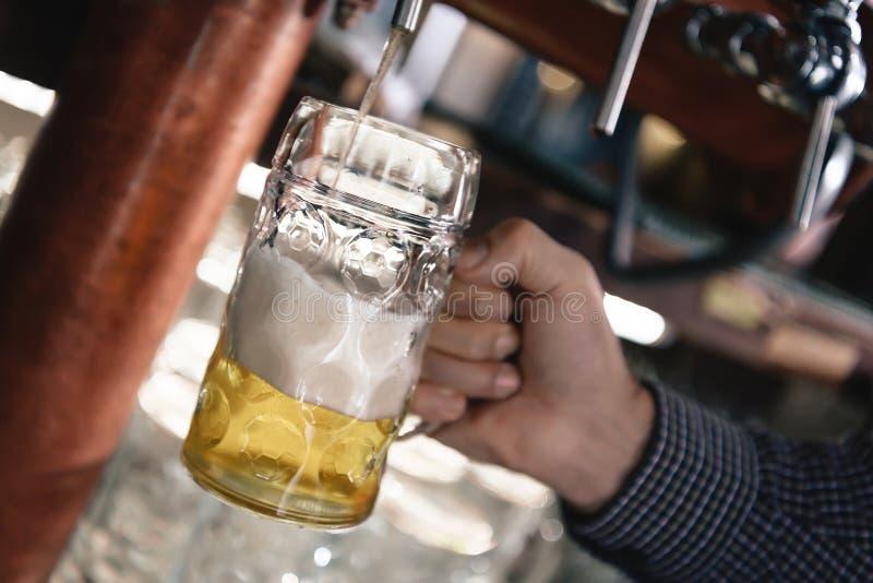 La taza de cerveza grande se llena de la cerveza del grifo de la cerveza El cervecero vierte la cerveza en el vaso imagen de archivo libre de regalías