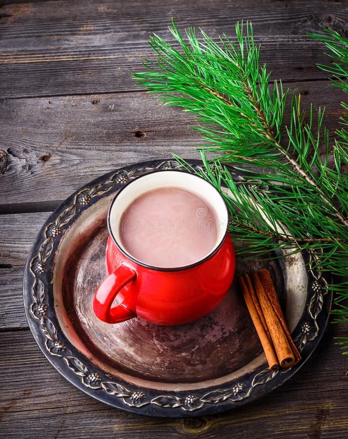 La taza de chocolate caliente y el pino ramifican en fondo de madera imagen de archivo libre de regalías