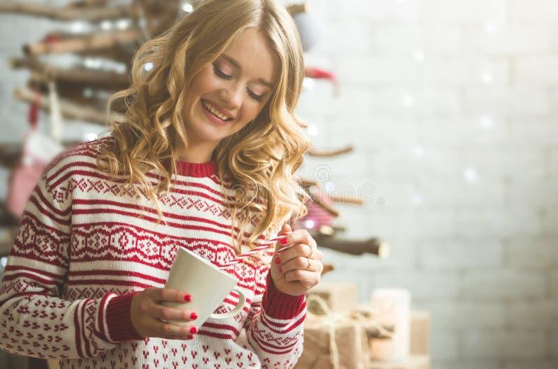 La taza de consumición hermosa joven de la mujer de café empañó el fondo del árbol de la nieve del invierno fotos de archivo