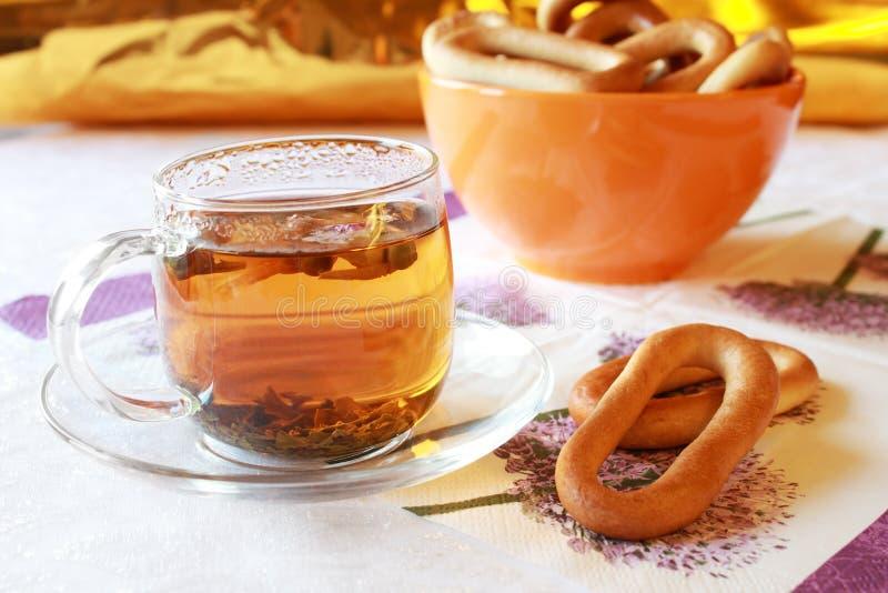 La taza de cristal de té con pan curruscante suena fotografía de archivo
