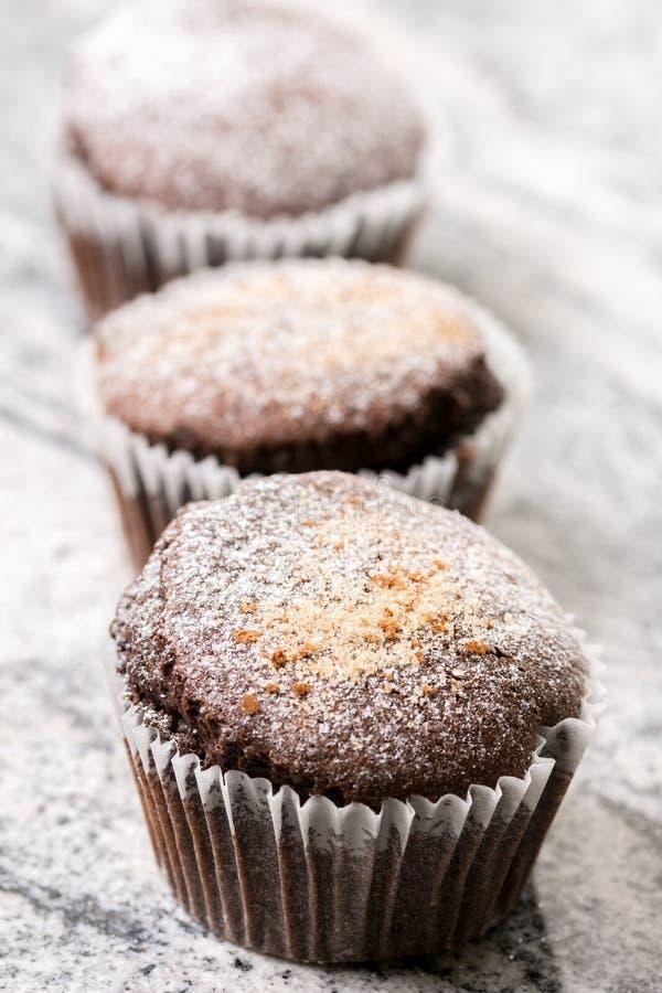 La taza de los brownie del chocolate se apelmaza con el azúcar en polvo en el fondo gris del granito foto de archivo
