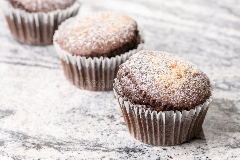 La taza de los brownie del chocolate se apelmaza con el azúcar en polvo en el fondo gris del granito fotografía de archivo libre de regalías