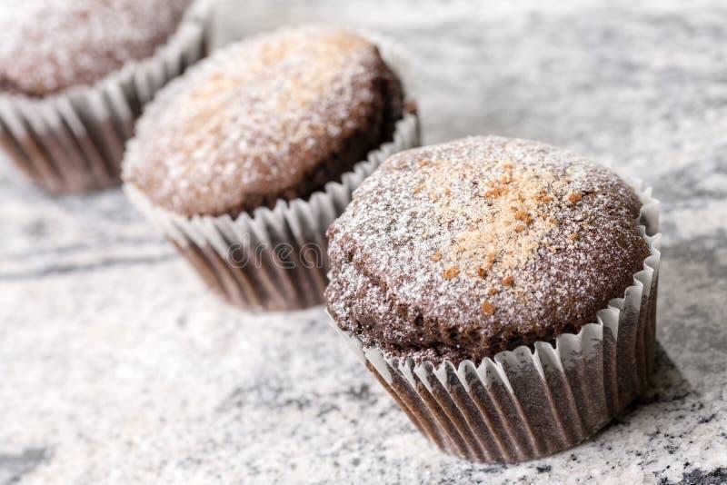 La taza de los brownie del chocolate se apelmaza con el azúcar en polvo en el fondo gris del granito imagenes de archivo