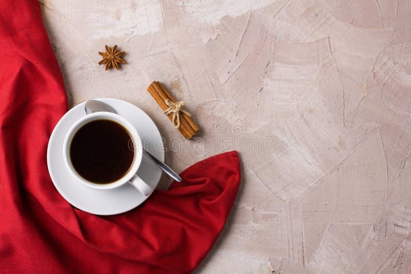 La taza de servilleta roja del café o del té condimenta el fondo concreto fotografía de archivo