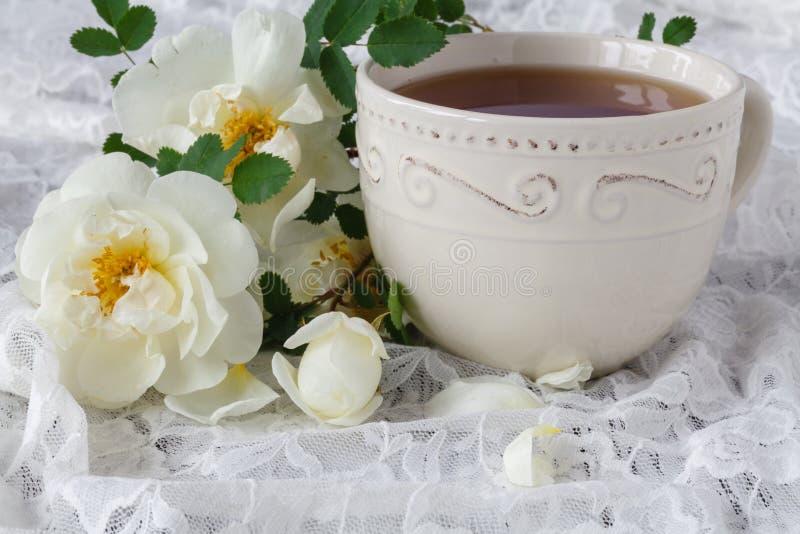 La taza de té caliente con salvaje subió, las flores florecientes frescas imágenes de archivo libres de regalías
