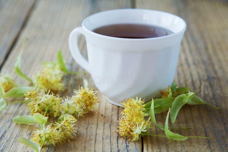 La taza de té con el tilo florece en una tabla imagenes de archivo