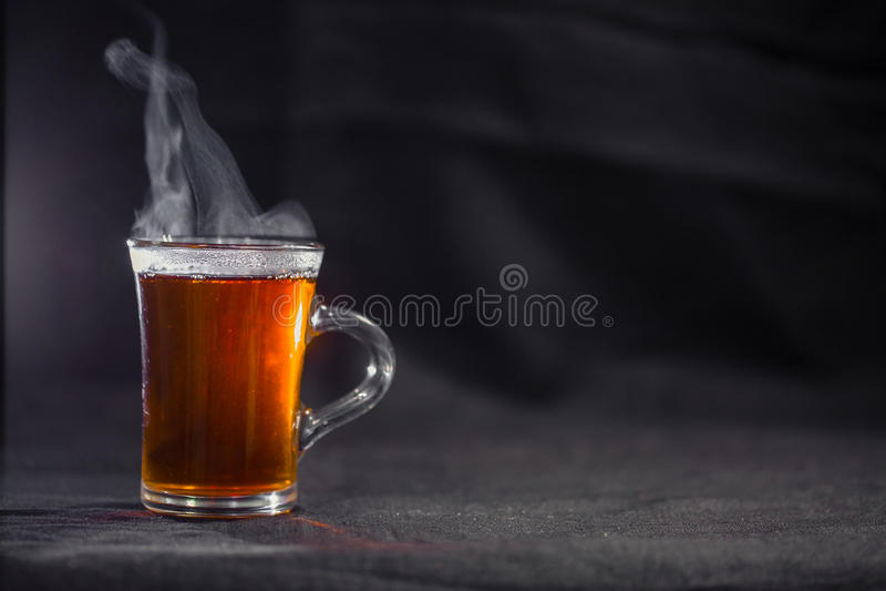 La taza de té en un fondo oscuro fotografía de archivo libre de regalías