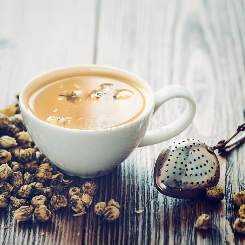 La taza de té sana de manzanilla, la taza de té sana de manzanilla del tamiz, el tamiz y la margarita seca florece imagenes de archivo