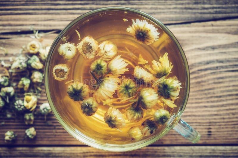 La taza de té sana de manzanilla y la margarita seca florece imágenes de archivo libres de regalías