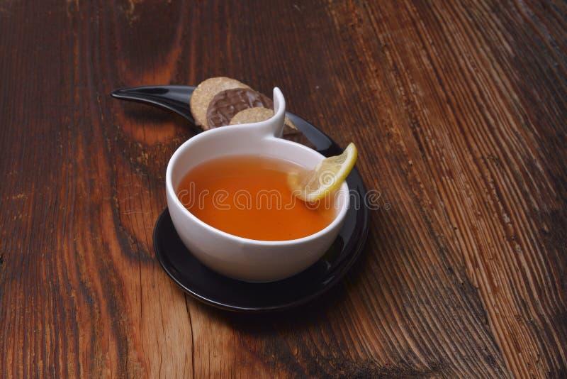 La taza de té y de galletas en la madera imagen de archivo libre de regalías