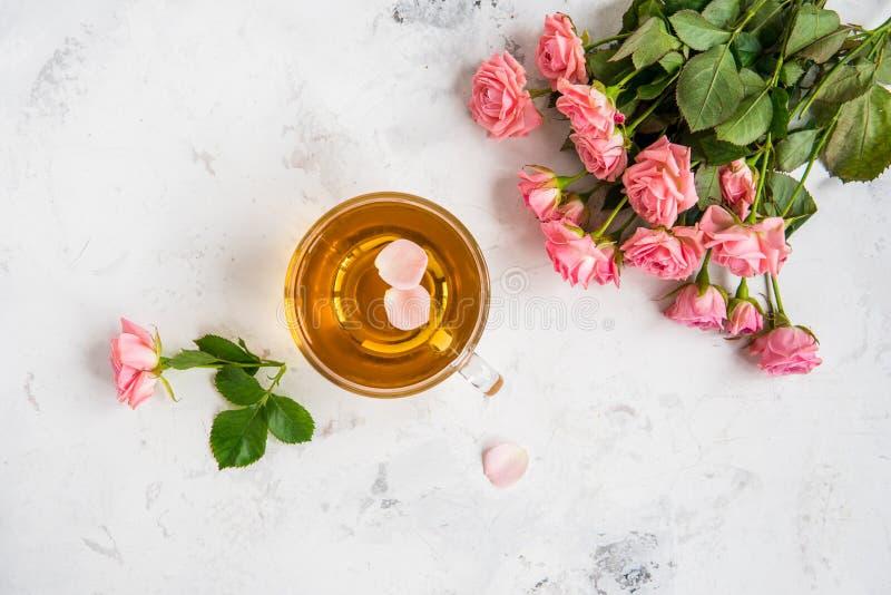 La taza de té y las rosas rosadas blandas en un fondo blanco copian el spac imagen de archivo