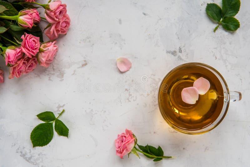 La taza de té y las rosas rosadas blandas en un fondo blanco copian el spac imagen de archivo libre de regalías