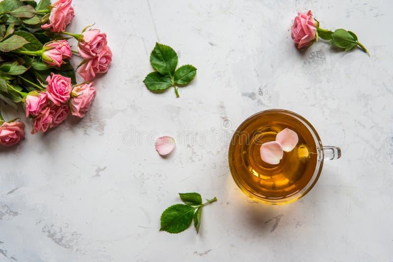 La taza de té y las rosas rosadas blandas en un fondo blanco copian el spac imágenes de archivo libres de regalías