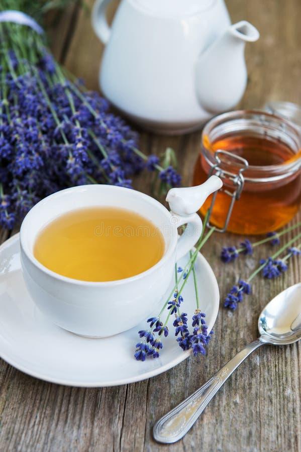 La taza de té y de miel con lavanda florece fotografía de archivo