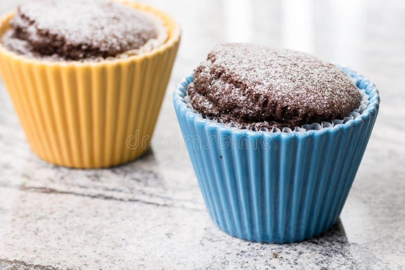 La taza del chocolate se apelmaza con el azúcar en polvo en los cuencos de la porcelana sobre fondo gris del granito fotografía de archivo