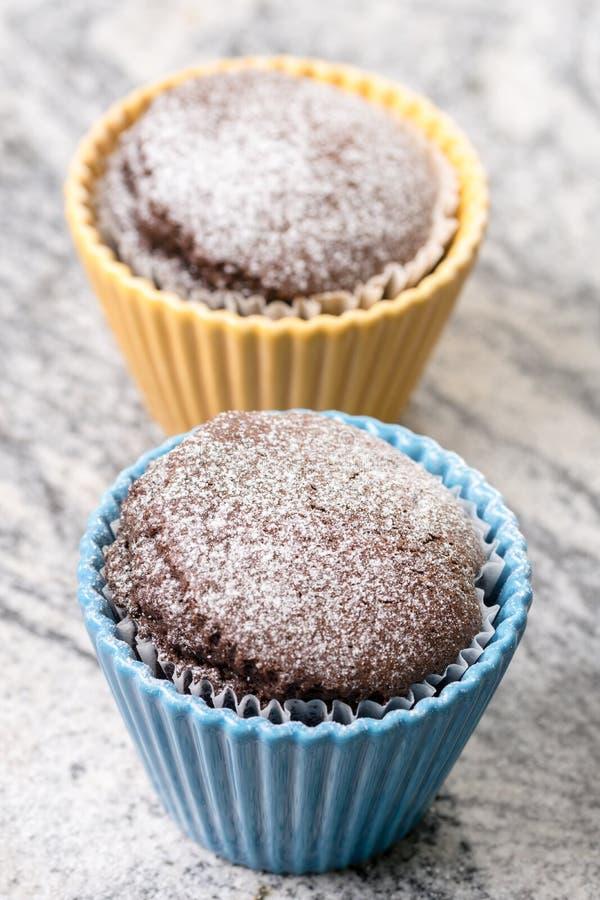 La taza del chocolate se apelmaza con el azúcar en polvo en los cuencos de la porcelana sobre fondo gris del granito imagenes de archivo