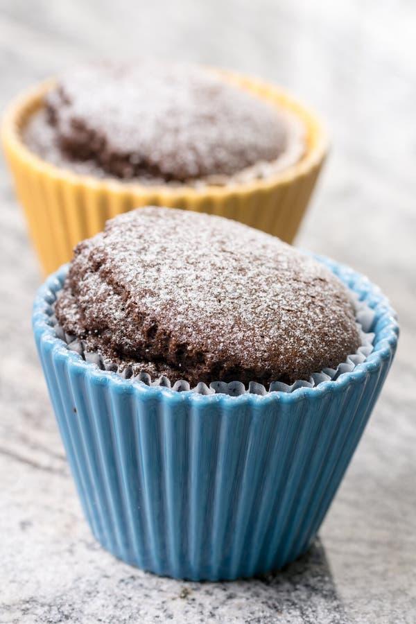 La taza del chocolate se apelmaza con el azúcar en polvo en los cuencos de la porcelana sobre fondo gris del granito imagen de archivo libre de regalías