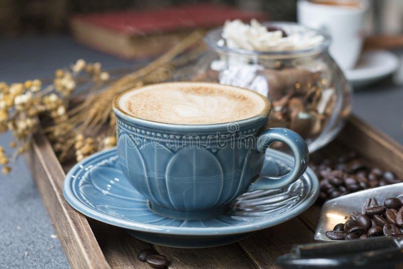 La taza del Latte, el grano de café, el libro y las flores secadas sacuden en de madera fotos de archivo libres de regalías