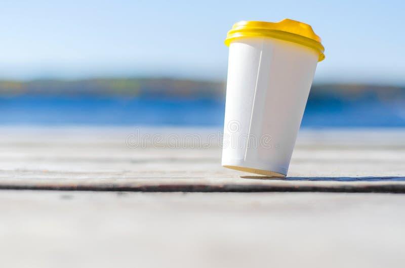 La taza del Libro Blanco con una tapa plástica amarilla se coloca en los tableros en la orilla del lago imágenes de archivo libres de regalías