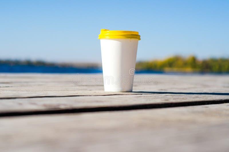 La taza del Libro Blanco con una tapa plástica amarilla se coloca en los tableros en la orilla del lago imagen de archivo libre de regalías