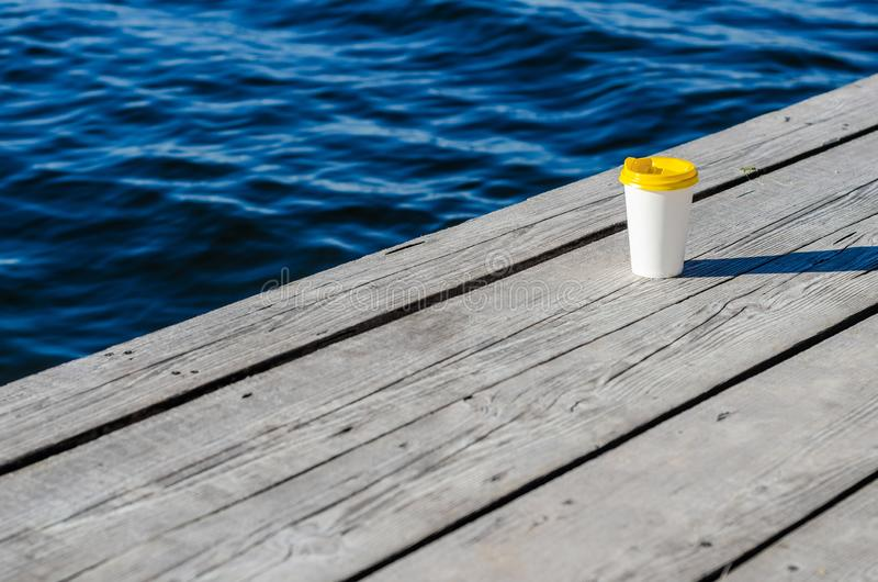 La taza del Libro Blanco con una tapa plástica amarilla se coloca en los tableros en la orilla del lago fotografía de archivo