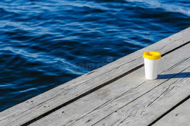 La taza del Libro Blanco con una tapa plástica amarilla se coloca en los tableros en la orilla del lago foto de archivo