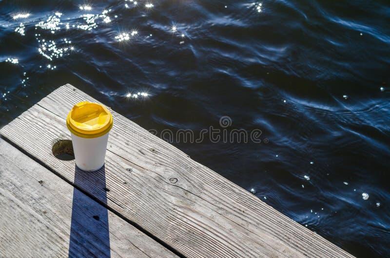 La taza del Libro Blanco con una tapa plástica amarilla se coloca en los tableros en la orilla del lago imagenes de archivo