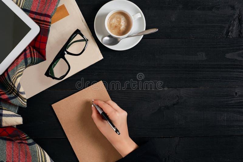 La taza del periódico y de café, vidrios de lectura, tableta, la mano está escribiendo en el papel de Kraft foto de archivo libre de regalías