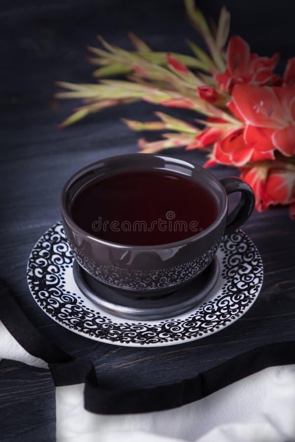 La taza negra con el gladiolo del té y del rojo de la fruta florece en un fondo de madera negro fotos de archivo