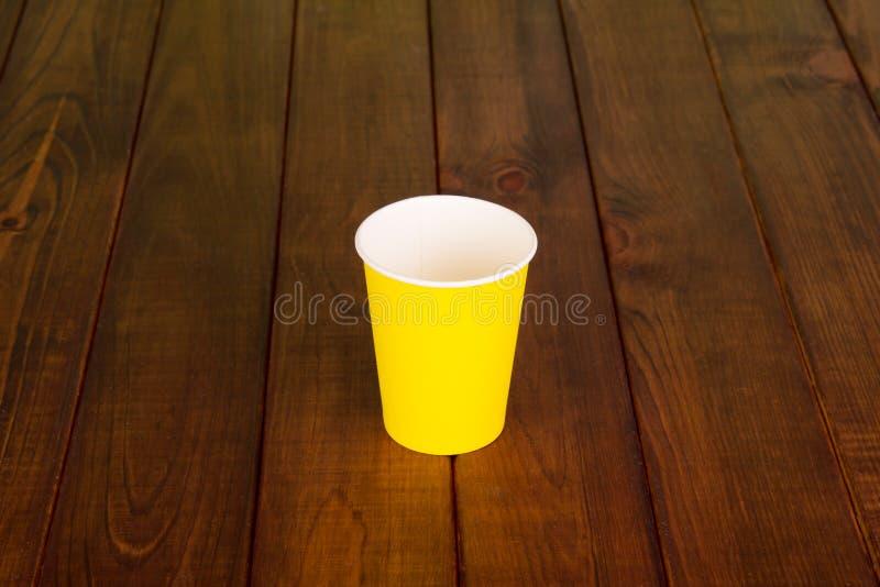 La taza plástica disponible se coloca en la tabla de madera imagen de archivo