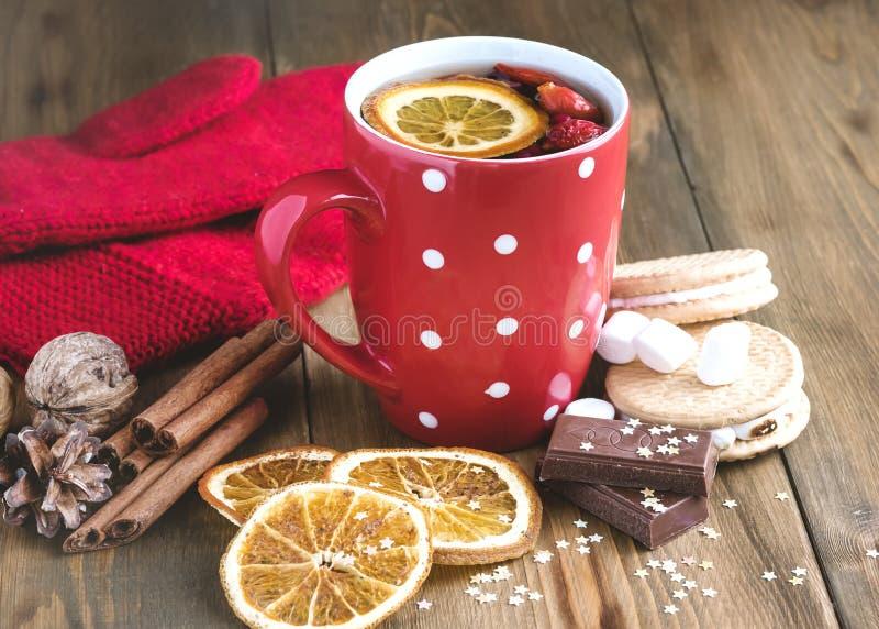 La taza roja de té caliente con los palillos de madera de Cinnamone del fondo del concepto de la comida de la Navidad de la bebid imagen de archivo