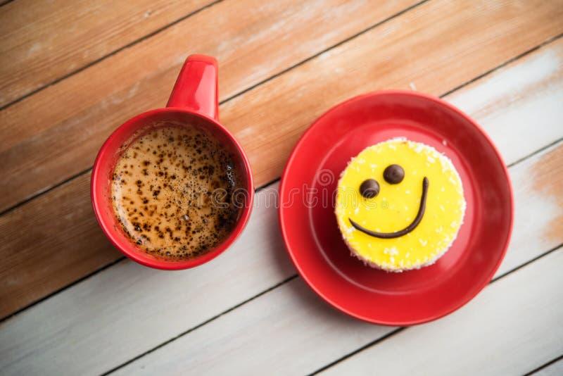 La taza roja y la sonrisa del café se apelmazan en la tabla de madera imagenes de archivo