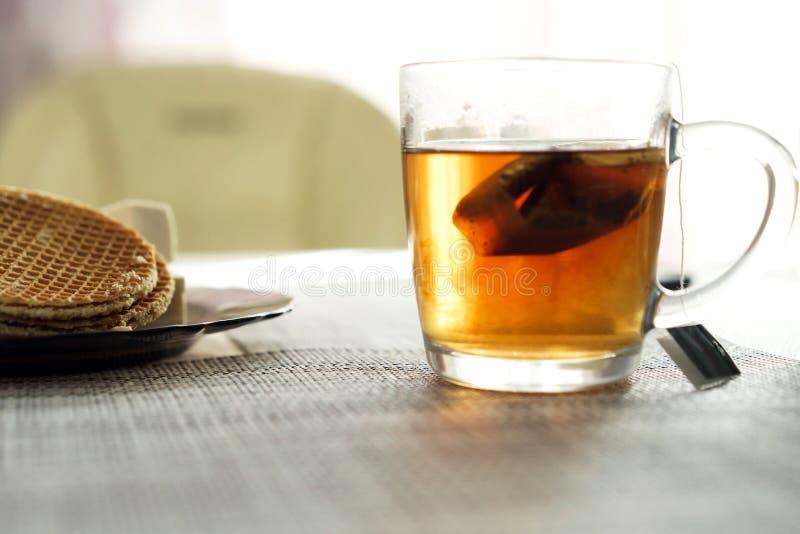 La taza transparente con la bolsita de té preparada está en la tabla al lado de la placa fotos de archivo libres de regalías