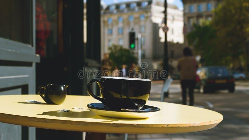 La taza y el platillo negros con el jarro de leche en un café de la calle presentan A fotografía de archivo