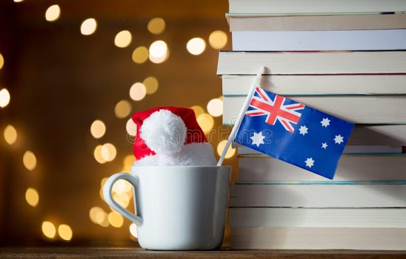 La taza y el sombrero blancos de la Navidad con Australia señalan por medio de una bandera cerca de los libros fotografía de archivo