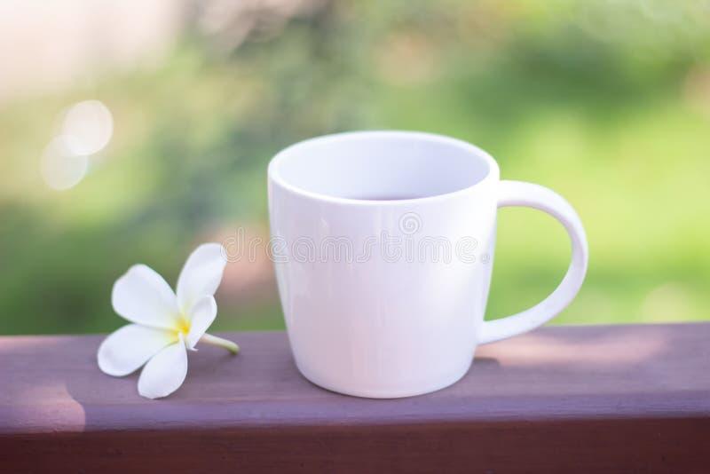La taza y la flor del café con leche del foco selectivo se colocan en piso de madera con el fondo borroso imagenes de archivo