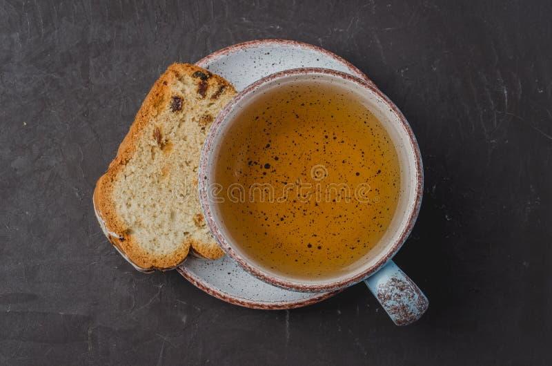 La taza y los pasteles blancos de té juntan las piezas en la tabla de piedra oscura Visi?n superior imagenes de archivo