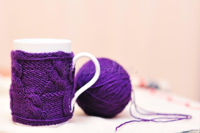 La tazza bianca con la viola ha tricottato il maglione con la palla di filato fotografia stock